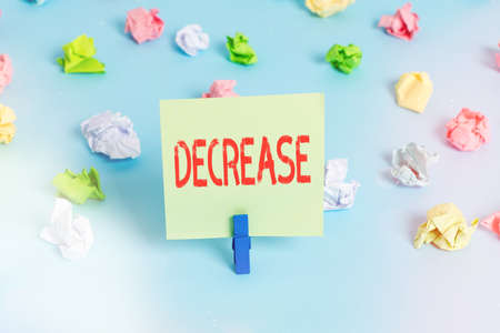 Word writing text Decrease. Business photo showcasing the process of growing progressively less in size, amount, etc. Colored crumpled papers empty reminder blue floor background clothespin Archivio Fotografico