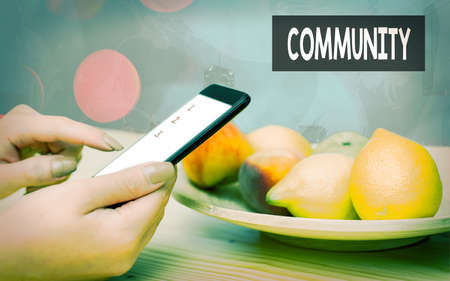 Handwriting text Community. Conceptual photo group of showing with a common characteristics living together Modern gadgets with white display screen under colorful bokeh background