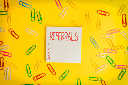 Writing note showing Referrals. Business concept for act, action, or an instance of referring to someone for work Flat lay above empty paper with copy space and colored paper clips