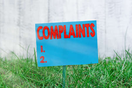 Handwriting text Complaints. Conceptual photo something that is the cause or subject of protest or outcry Plain empty paper attached to a stick and placed in the green grassy land 写真素材