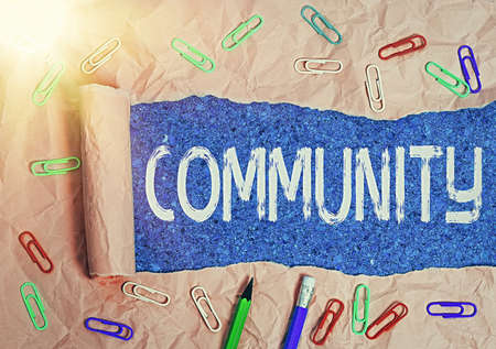 Text sign showing Community. Business photo text with a common characteristic or interest living together Rolled ripped torn cardboard placed above a wooden classic table backdrop