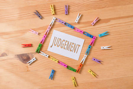 Writing note showing Judgement. Business concept for process of forming an evaluation by discerning and comparing Colored clothespin papers empty reminder wooden floor background office Imagens