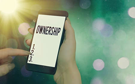 Conceptual hand writing showing Ownership. Concept meaning the state, relation, or fact of being an owner or with a group Modern gadgets white screen under colorful bokeh background