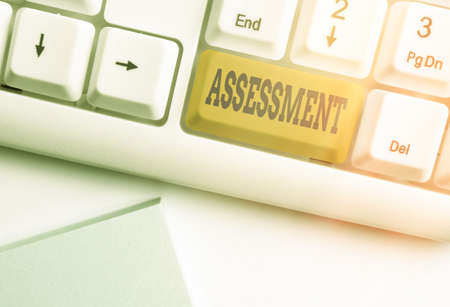 Text sign showing Assessment. Business photo text action or an instance of making a judgment about something Different colored keyboard key with accessories arranged on empty copy space