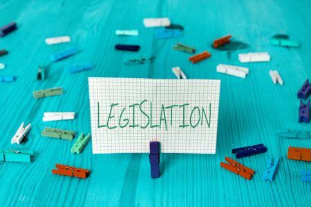 Conceptual hand writing showing Legislation. Concept meaning the exercise of the power and function of making rules Colored crumpled rectangle shape paper light blue background