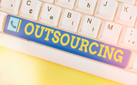 Conceptual hand writing showing Outsourcing. Concept meaning obtain goods or a service from an outside or foreign supplier Colored keyboard key with accessories arranged on empty copy space