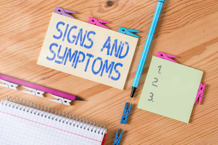 Conceptual hand writing showing Signs And Symptoms. Concept meaning abnormalities that indicate a likely medical condition Colored crumpled papers wooden floor background clothespin
