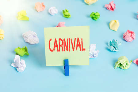 Word writing text Carnival. Business photo showcasing traveling enterprise offering amusements, exhibitions, etc. Colored crumpled papers empty reminder blue floor background clothespin