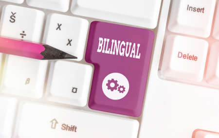 Writing note showing Bilingual. Business concept for using or able to use two languages especially with equal fluency Colored keyboard key with accessories arranged on empty copy space Imagens
