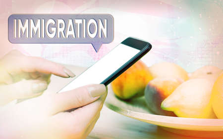 Word writing text Immigration. Business photo showcasing the action of coming to live permanently in a foreign country Modern gadgets with white display screen under colorful bokeh background