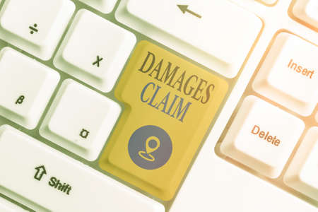 Conceptual hand writing showing Damages Claim. Concept meaning seeks to repair the damages or liability of the victim party Colored keyboard key with accessories arranged on empty copy space