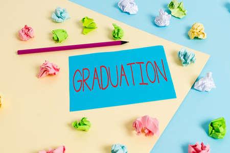 """写写""""毕业""""的纸条。奖励或接受学位或文凭的经营理念彩色皱巴巴的纸空提醒蓝色黄色晒衣夹"""