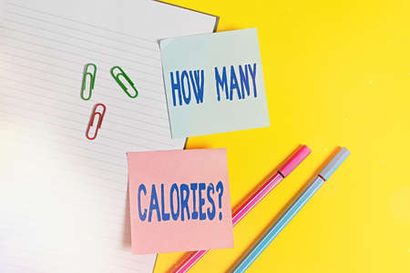 Handwriting text How Many Calories Question. Conceptual photo asking how much energy our body could get from it Empty blue paper with copy space paper clips and pencils on the yellow table