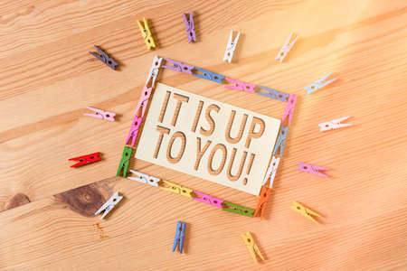 Word writing text It Is Up To You. Business photo showcasing Used to tell an individual that they are the one to decide Colored clothespin papers empty reminder wooden floor background office