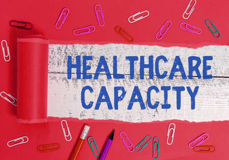 Writing note showing Healthcare Capacity. Business concept for maximum amount of patients provided with the right medical service Rolled ripped torn cardboard above a wooden classic table