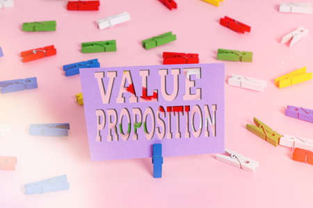 Handwriting text writing Value Proposition. Conceptual photo feature intended to make a company or product attractive Colored clothespin papers empty reminder pink floor background office pin