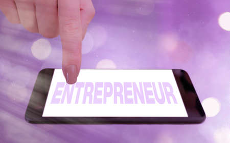 Conceptual hand writing showing Entrepreneur. Concept meaning one who organizes and assumes the risks of a business Modern gadgets white screen under colorful bokeh background Stock fotó