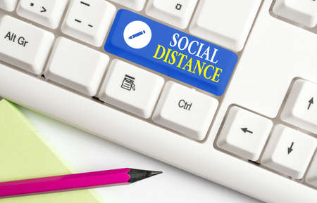 Conceptual hand writing showing Social Distance. Concept meaning maintaining a high interval physical distance for public health safety Colored keyboard key with accessories arranged on empty copy space Imagens