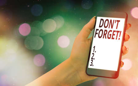 Conceptual hand writing showing Don T Forget. Concept meaning used to remind someone about an important fact or detail Modern gadgets white screen under colorful bokeh background