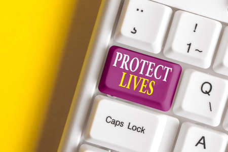 Conceptual hand writing showing Protect Lives. Concept meaning to cover or shield from exposure injury damage or destruction Colored keyboard key with accessories arranged on copy space Banque d'images