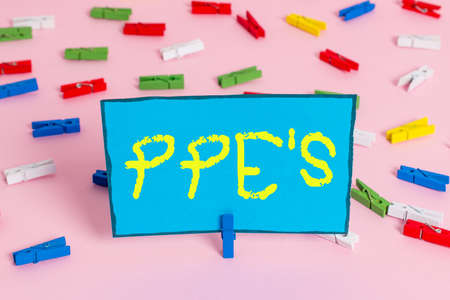 Text sign showing Ppe's is. Business photo showcasing Specialized equipment for protection against health and safety hazard Colored clothespin papers empty reminder pink floor background office pin