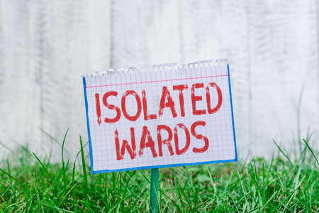 Word writing text Isolated Wards. Business photo showcasing far away from places or showing and having minimal contact Mathematic paper attached to a stick and placed in the green grassy land