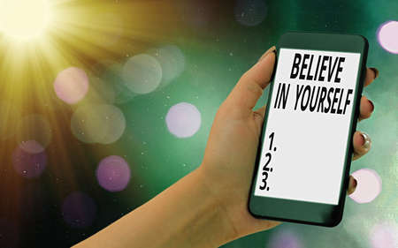 Conceptual hand writing showing Believe In Yourself. Concept meaning common piece of advice that you can do everything Modern gadgets white screen under colorful bokeh background