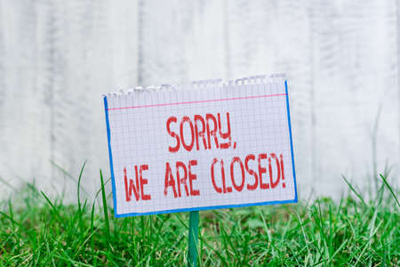 Word writing text Sorry, We Are Closed. Business photo showcasing apologize for shutting off business for specific time Mathematic paper attached to a stick and placed in the green grassy land Banque d'images