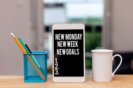 Handwriting text New Monday New Week New Goals. Conceptual photo showcasing next week resolutions To do list Paper accesories with digital smartphone arranged on different background