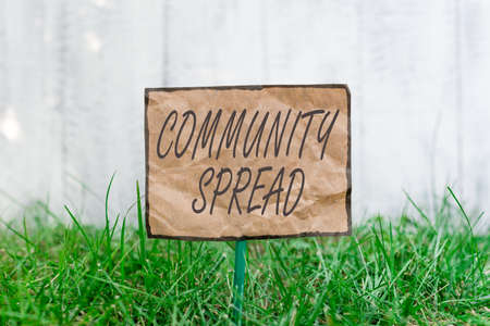 Handwriting text writing Community Spread. Conceptual photo dissemination of a highlycontagious disease within the local area Crumpled paper attached to a stick and placed in the green grassy land