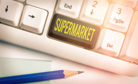 Text sign showing Supermarket. Business photo text organized selfservice shop offering wide variety of product Different colored keyboard key with accessories arranged on empty copy space