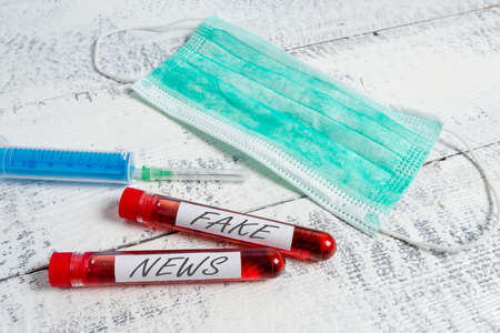 Text sign showing Fake News. Business photo showcasing false information publish under the guise of being authentic news Extracted blood sample vial with medical accessories ready for examination