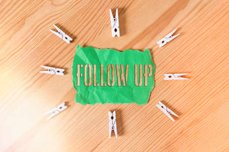 Text sign showing Follow Up. Business photo text a continuation of something that has already been started Colored clothespin papers empty reminder wooden floor background office Foto de archivo