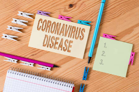 Writing note showing Coronavirus Disease. Business concept for defined as illness caused by a novel virus SARSCoV2 Colored clothespin papers empty reminder wooden floor background office