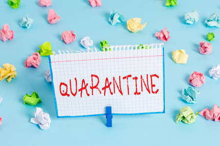 Handwriting text Quarantine. Conceptual photo restraint upon the activities of an individual or the transport of goods Colored crumpled papers empty reminder blue floor background clothespin