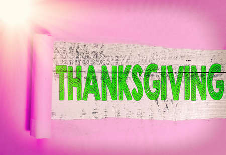 Text sign showing Thanksgiving. Business photo showcasing public acknowledgment or celebration of divine goodness Rolled ripped torn cardboard placed above a wooden classic table backdrop Foto de archivo