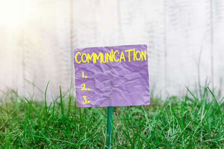Conceptual hand writing showing Communication. Concept meaning information is exchanged between individuals through a system Plain paper attached to stick and placed in the grassy land