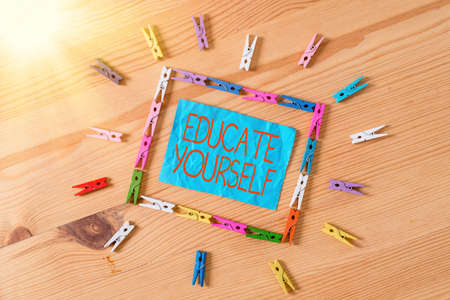 Conceptual hand writing showing Educate Yourself. Concept meaning prepare oneself or someone in a particular area or subject Colored crumpled papers wooden floor background clothespin Stockfoto