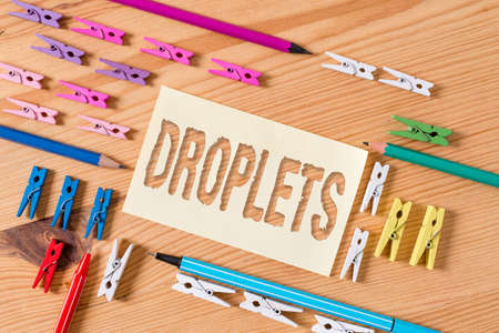 Handwriting text Droplets. Conceptual photo very small drop of a liquid can be found in certain wet places Colored clothespin papers empty reminder wooden floor background office