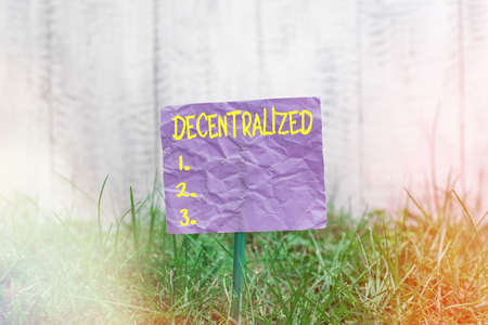 Conceptual hand writing showing Decentralized. Concept meaning move departments away from a single administrative center Plain paper attached to stick and placed in the grassy land