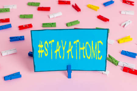 Text sign showing Hashtag Stay at home. Business photo showcasing a trending label in social media related to the coronvirus outbreak Colored clothespin papers empty reminder pink floor background office pin