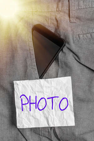 Text sign showing photo. Business photo text defined as produced by light, image taken with the help of light. Smartphone device inside formal work trousers front pocket near note paper