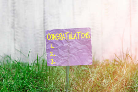 Conceptual hand writing showing Congratulations. Concept meaning a congratulatory expression usually used in plural form Plain paper attached to stick and placed in the grassy land