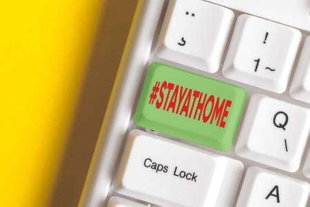 Writing note showing Hashtag Stay at home. Business concept for a trending label in social media related to the coronvirus outbreak Colored keyboard key with accessories arranged on empty copy space 版權商用圖片