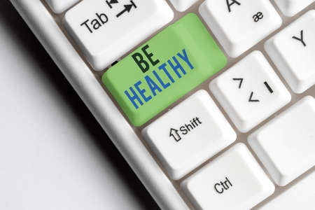 Writing note showing Be Healthy. Business concept for promote a state of complete emotional and physical wellbeing Colored keyboard key with accessories arranged on empty copy space