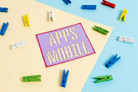 Handwriting text Apps Mobile. Conceptual photo computer program designed to run on phone hand held device Colored clothespin paper empty reminder yellow blue floor background office