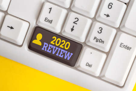 Handwriting text 2020 Review. Conceptual photo seeing important events or actions that made previous year Different colored keyboard key with accessories arranged on empty copy space 스톡 콘텐츠