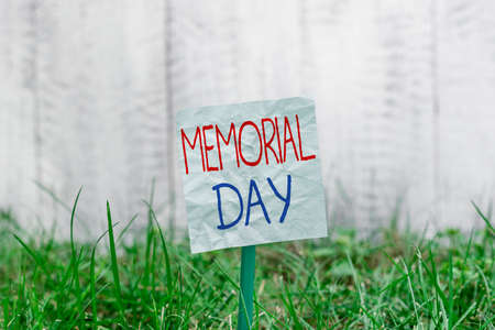Handwriting text Memorial Day. Conceptual photo To honor and remembering those who died in military service Plain empty paper attached to a stick and placed in the green grassy land 写真素材