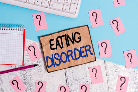 Writing note showing Eating Disorder. Business concept for illnesses or severe disturbances in their eating behaviors Writing tools and scribbled paper on top of the wooden table