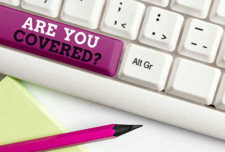 Word writing text Are You Covered Question. Business photo showcasing asking if they had insurance in work or life Different colored keyboard key with accessories arranged on empty copy space